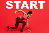 Motivated athlete girl in ready pose before running with lettering start