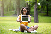 Happy African American girl showing tablet computer with empty screen at park, space for design