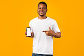 Positive Black Guy Showing Phone Empty Screen On Yellow Background