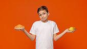 Pensive teenager choosing between croissant and fresh pear