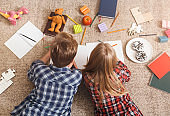 Unrecognizable Brother And Sister Drawing Together Lying On Floor