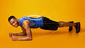 Fit African American man doing plank exercise on orange background, collage. Panorama