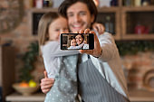 Happy dad and daughter taking selfie on smartphone while cooking at kitchen
