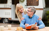 Mature woman hugging her husband while he solving crossword during breakfast at campsite
