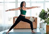 Beautiful Hispanic woman doing her yoga strength training in living room. Warrior pose