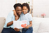 Afro kid congratulating her mom on the sofa