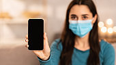 Woman wearing surgical mask showing smart phone