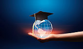 Hand outstreching globe hologram with graduation hat