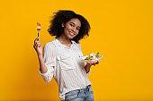 Cheerful Afro Girl Eating Fresh Vegetable Salad, Posing Over Yellow Background