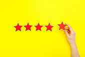 5 stars increase rating, customer experience concept. Hand of client show putting 5 star symbol to increase Service rating. five red stars excellent rating on yellow background. Satisfaction concept
