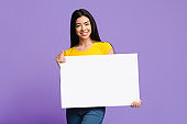 Smiling Asian Female Holding Blank White Placard In Hands Over Purple Background