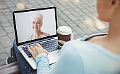 Girl making video call on laptop outdoors, chatting with granny