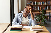 African American guy with books exhausted from studying or working at urban cafe