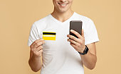 Cheerful millennial man in white t-shirt looks at smartphone and holds credit card, pays for purchase