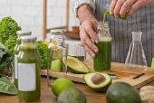 Man vegetarian adding green extract to detox smoothie