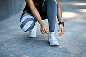 Closeup of black girl in sportswear tying shoelaces before jogging