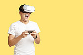 Happy young man with open mouth in virtual reality glasses holds smartphone and play