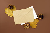 Envelope and letter, cones and dried orange leaves flat lay on brown background top view, copy space. Autumn decorations. Holidays invitations. Creative composition. Stock photo.
