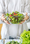 Unrecognizable woman preparing a green mixed salad in the kitchen