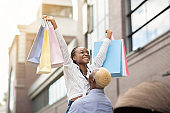 Dreams come true. Happy african american guy lifts up girl with colorful bags and have fun on street