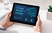 Woman using digital tablet with home security application