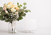 Still life roses in wedding bouquet and easel for creative text