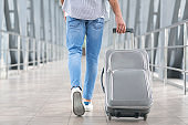 Transit Passenger Concept. Unrecognizable Man Walking With Suitcase In Airport Terminal