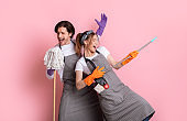 Playful couple of cleaners fooling together while making spring tidying