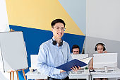 Happy Asian male helpdesk operator in headset holding documents at modern office