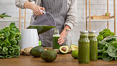 Woman in linen apron pouring smoothie drink from blender to bottle