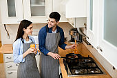 Couple preparing dinner frying on pan at home