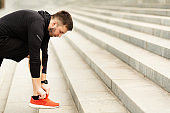 Closeup of Young Man Tying Sports Shoe In City