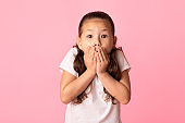Portrait of amazed asian girl covering her mouth with hands