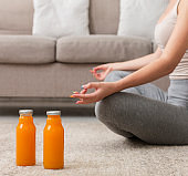 Unrecognizable young woman doing yoga at home and drinking fresh juice