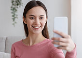 Young cheerful girl recording video vlog on a mobile phone
