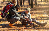 Black guy helping his injured friend, hiking together