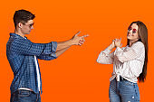 Cheerful millennial male and female in sunglasses making finger imaginary gun gesture
