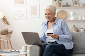Online Payments. Senior Woman Using Laptop And Credit Card At Home