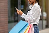 Best offer from shops. Happy african american woman with bags leave reviews of store