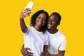 Happy african american couple taking selfie on smartphone
