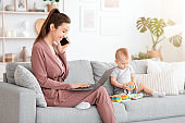 Working Mom. Young Woman Freelancer Using Cellphone And Laptop Next To Baby