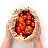 Woman holds eco paper bag full of fresh tomatoes