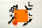 Halloween background with paper bats, spiders,jack-o'-lantern on white wooden background. Halloween holiday decorations. Flat lay, top view, copy space. Party invitation mockup, celebration.