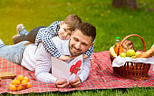 Celebrating Father Day. Young father excited to read his son's greeting card during picnic in countryside