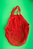 Red shopping mesh bag on green background. Zero waste concept and plastic free concept.