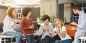 Young creative team cheering new comer girl in office