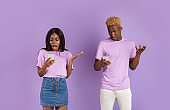Shocked black girl and African American guy looking into smartphones on violet background