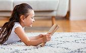 Happy Kid Girl Reading Book Smiling Lying On Floor Indoors