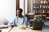 Millennial African American guy with smartphone and laptop enjoying morning coffee and croissant in cafe