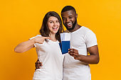 Smiling multiracial couple holding passports with boarding passes, ready to travel